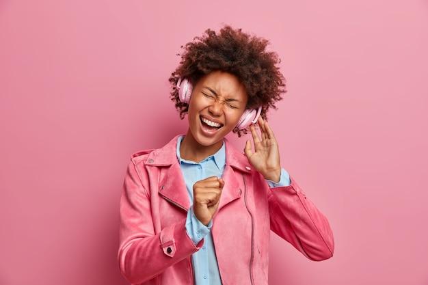Vrolijke afro-amerikaanse vrouw houdt hand als microfoon, zingt luid lied, luistert naar muziek via koptelefoon, kantelt hoofd, dwazen rond, gekleed in modieus jasje