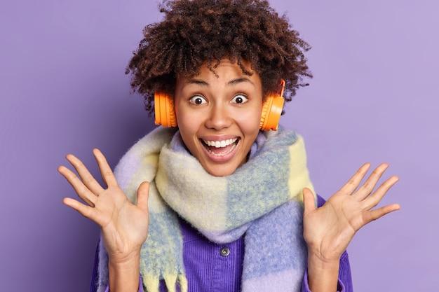 Vrolijke afro-amerikaanse vrouw kijkt met erg blij opgewonden uitdrukking verhoogt handen geniet van het luisteren naar favoriete muziek via stereo koptelefoon draagt warme sjaal om nek.