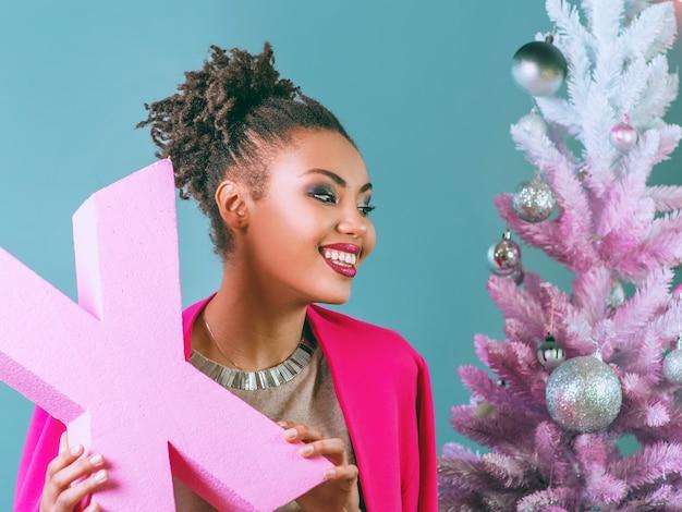 Vrolijke afro-amerikaanse vrouw met roze letter x in haar handen op de achtergrond van de kerstboom