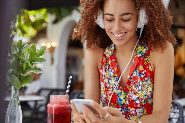 Vrolijke afro-amerikaanse vrouw met tevreden uitdrukking maakt gebruik van moderne koptelefoons, luistert naar nieuw populair liedje of surft op de website van de radio op slimme telefoon