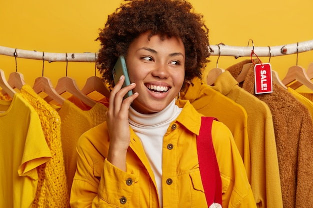 Vrolijke afro-amerikaanse vrouw praat op mobiele telefoon, checkt wat kleren in de winkel, poses over kledingrek, sharaes wat de verkoop in de winkel is