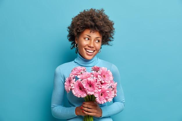 Vrolijke afro-amerikaanse vrouw viert haar speciale dag, houdt boeket roze bloemen vast, aanbidt gerbera's, glimlacht breed, draagt coltrui,