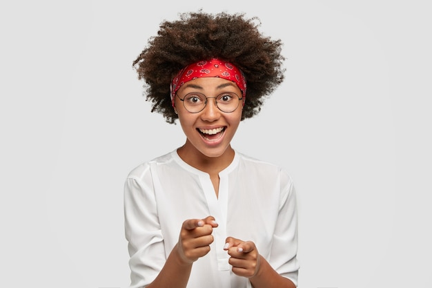 Vrolijke afro-amerikaanse vrouw wijst met beide wijsvingers, drukt haar keuze uit, heeft krullend haar en een donkere huid, draagt een ronde bril, casual shirt, geïsoleerd over witte muur