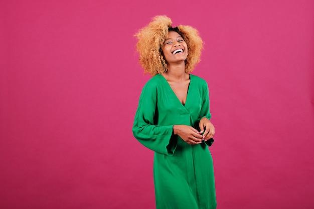 Vrolijke afro-vrouw die een groene jurk draagt en lacht terwijl ze poseert tegen een geïsoleerde achtergrond.