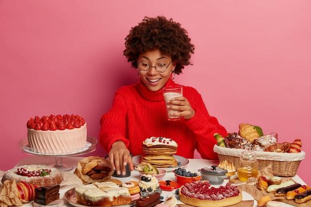 Vrolijke afro-vrouw strekt zich uit naar een heerlijk dessert, houdt een glas melk vast, eet cake, omringd met junkfood, draagt een bril en een rode trui, kan geen nee zeggen tegen snoep