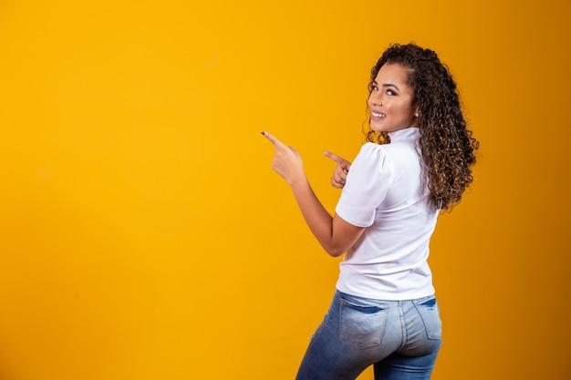 Vrolijke afrovrouw wijst naar kopieerruimte, bespreekt geweldige promo, geeft plaats of richting. vrouw met haar rug naar de zijkant gericht