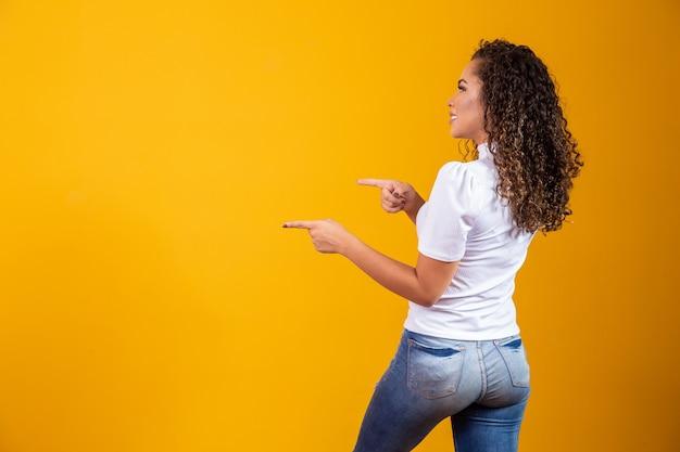 Vrolijke afrovrouw wijst naar kopieerruimte, bespreekt geweldige promo, geeft plaats of richting. vrouw met haar rug naar de zijkant gericht Premium Foto