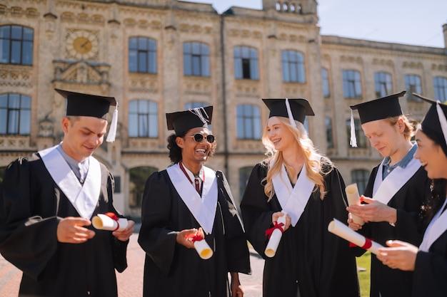Vrolijke afstuderende studenten die naar hun diploma's kijken en blij zijn ze eindelijk te hebben