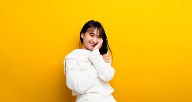 Vrolijke alledaagse foto van een gelukkig meisje dat op een gele achtergrond staat kijkend naar de camera en vrolijk glimlacht