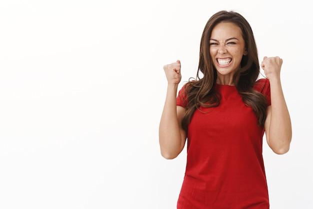 Vrolijke ambitieuze jonge brunette mooie vrouw behaalt succes, triomfeert eindelijk doel, vuist pomp vreugdevol, viert goed nieuws, staande witte muur