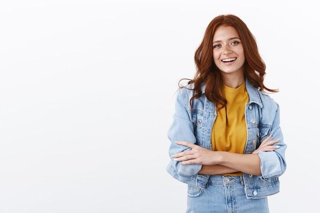 Vrolijke ambitieuze roodharige vrouw in spijkerjasje kruist armen in zelfverzekerde pose, glimlachend volbracht en zelfverzekerd, staande witte muur