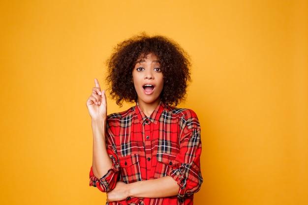 Vrolijke amerikaanse zwarte in rood overhemd die op camera kijken en vinger op exemplaarruimte benadrukken die over oranje achtergrond wordt geïsoleerd.