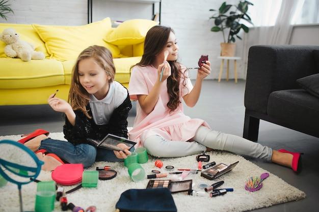 Vrolijke ans verlaten meisjes die op vloer in ruimte zitten. ze doen make-up. tieners kijken in de spiegel en gebruiken cosmetica.