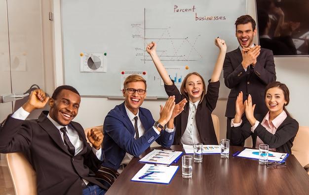Vrolijke arbeiders die zich in een bedrijfsbureau verheugen.