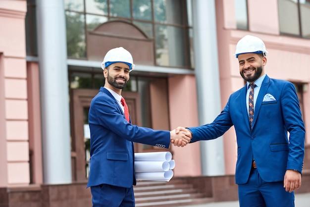 Vrolijke architecten in bouwvakkers die elkaar de hand schudden na hun ontmoeting