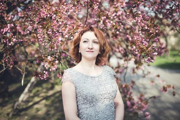 Vrolijke armeense vrouw onder de bloeiende sakura