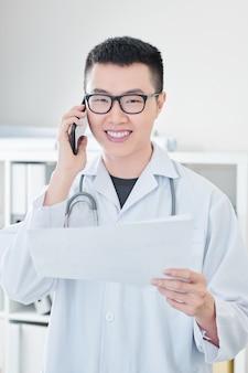 Vrolijke arts die de telefoon roept