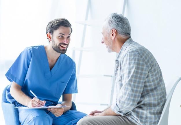 Vrolijke arts die met bejaarde patiënt spreekt