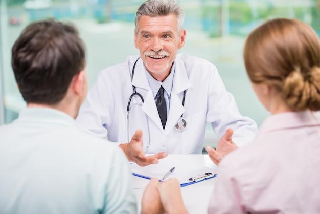 Vrolijke arts die met familiepaar bij kliniek spreken.
