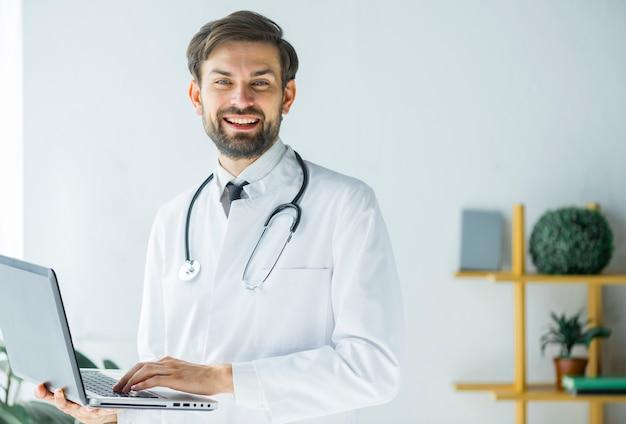 Vrolijke arts die met laptop camera bekijkt