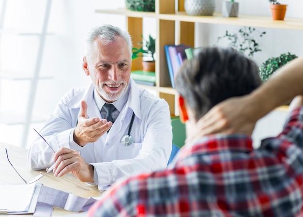 Vrolijke arts die met patiënt spreekt