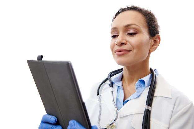Vrolijke arts met een stethoscoop om haar nek met digitale tablet op handen geïsoleerd op een witte achtergrond met kopie ruimte