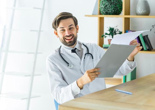 Vrolijke arts met klembord in office
