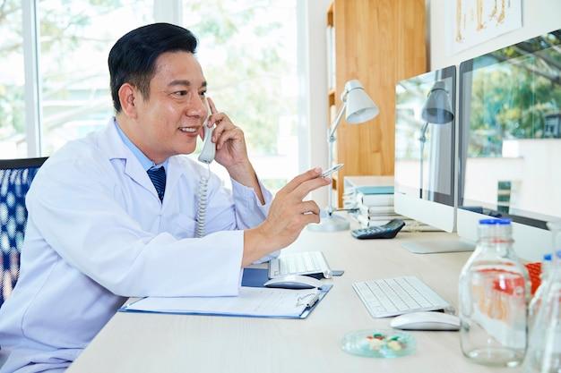 Vrolijke arts praten over de telefoon