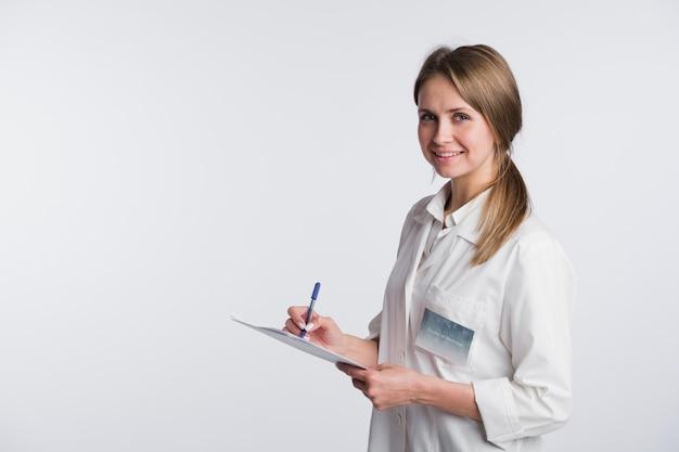 Vrolijke arts vrouw maken van aantekeningen. op wit wordt geïsoleerd