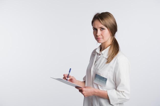 Vrolijke arts vrouw maken van aantekeningen.