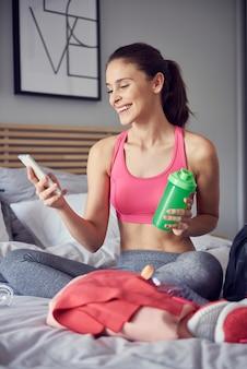 Vrolijke atleet met behulp van een mobiele telefoon in de slaapkamer