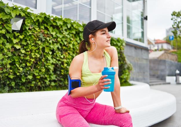 Vrolijke atletische vrouw drinkt water uit de fles en luistert naar muziek tijdens de trainingspauze buitenshuis