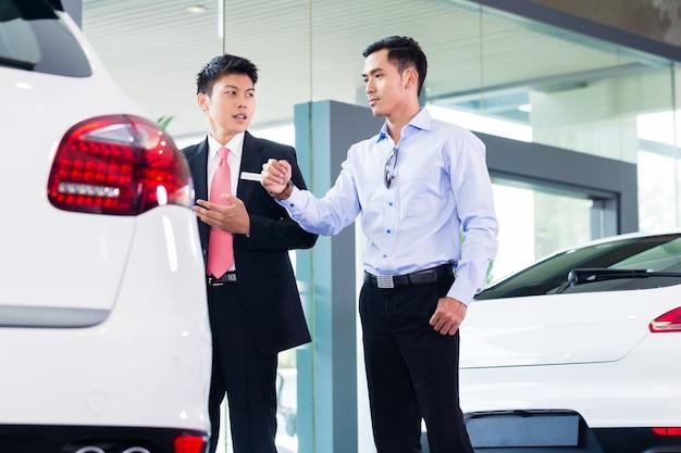 Vrolijke aziatische autoverkoper die auto aan klant verkoopt