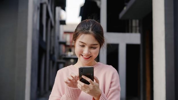Vrolijke aziatische backpacker blogger vrouw met behulp van smartphone voor richting en kijken op de kaart van de locatie tijdens het reizen op chinatown in peking, china. lifestyle rugzak toeristische reizen vakantie concept.
