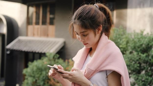 Vrolijke aziatische backpacker blogger vrouw met behulp van smartphone voor richting en kijken op de kaart van de locatie tijdens het reizen op chinatown in peking, china.