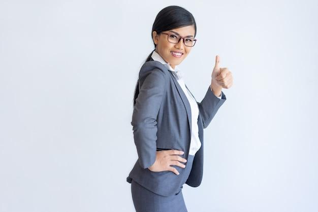 Vrolijke aziatische bedrijfsdame die product adviseert