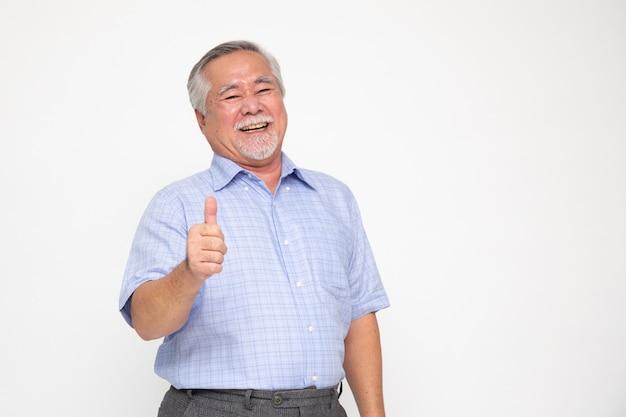 Vrolijke aziatische hogere mens die een duim opgeeft en de camera bekijkt die op wit wordt geïsoleerd