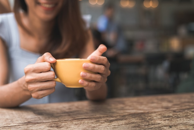 Vrolijke aziatische jonge vrouw die warme koffie of thee drinkt die van het geniet terwijl het zitten in koffie