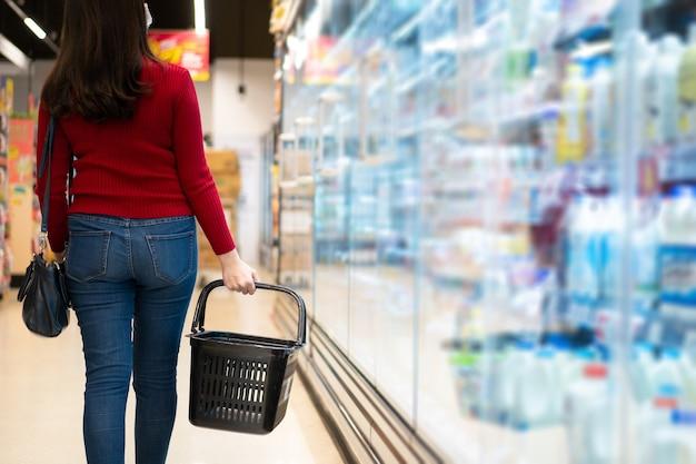 Vrolijke aziatische jonge vrouw met een winkelmandje in de supermarkt