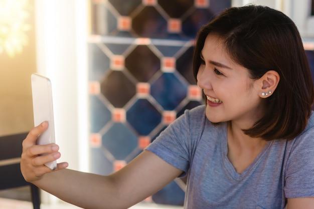 Vrolijke aziatische jonge vrouwenzitting in koffie die smartphone voor spreken, lezing en het texting gebruiken