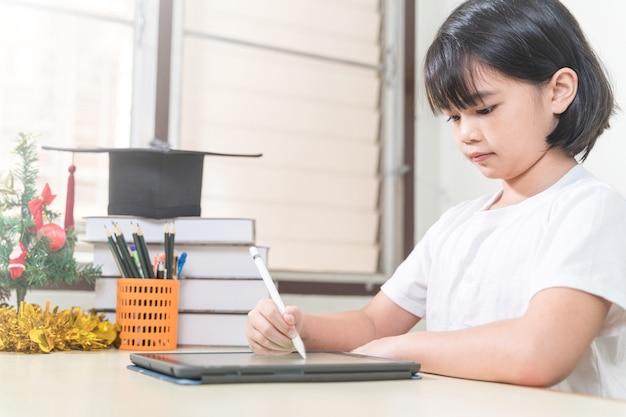 Vrolijke aziatische kleine studente draagt koptelefoon schrijft op digitale tablet om thuis te studeren
