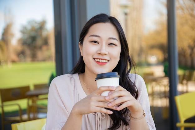 Vrolijke aziatische koffieminnaar die van ochtend geniet
