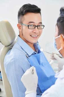 Vrolijke aziatische man bij tandarts