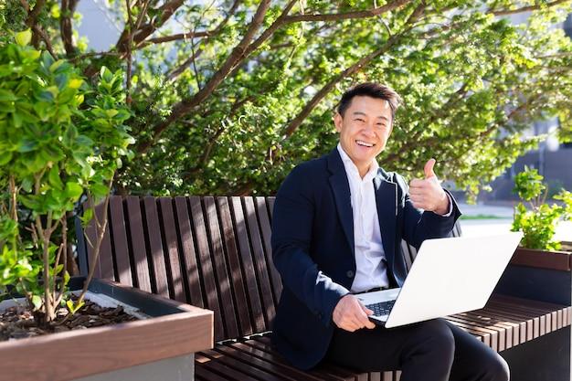 Vrolijke aziatische man die naar de camera kijkt en een glimlachende zakenman die aan een laptop werkt die op een bankje in de buurt van het kantoor op pauze zit