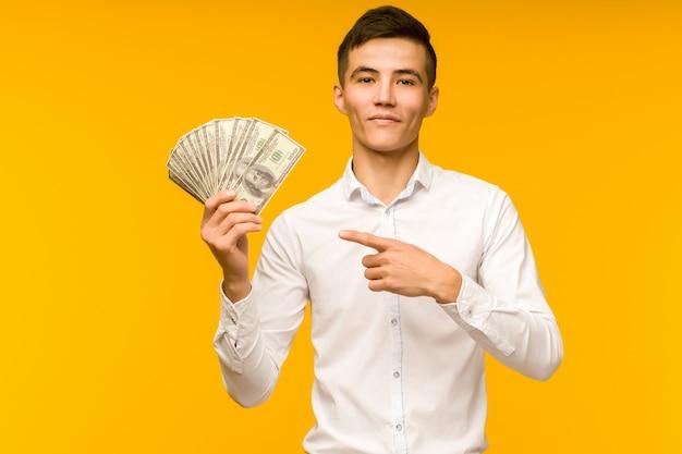 Vrolijke aziatische man in een wit overhemd wijst met een vinger naar geld dollars op een gele achtergrond