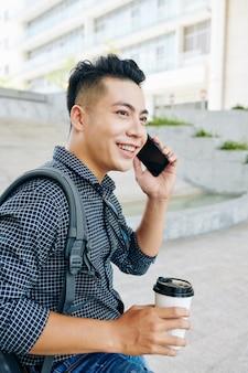 Vrolijke aziatische man praten over de telefoon