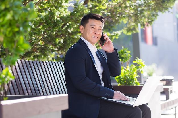 Vrolijke aziatische man zakenman die op laptop werkt en aan de telefoon praat, glimlachend zittend op een bankje in de buurt van het kantoor tijdens de lunchpauze