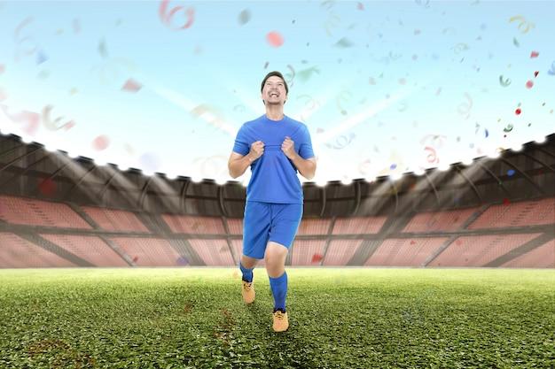 Vrolijke aziatische mannelijke voetballer vieren