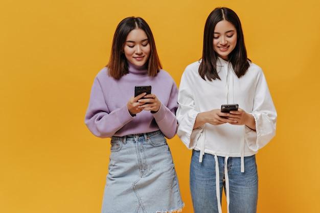 Vrolijke aziatische meisjes houden telefoons op oranje muur
