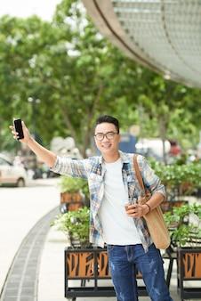 Vrolijke aziatische mens die zich naast weg bevindt en hand met smartphone uitsteekt